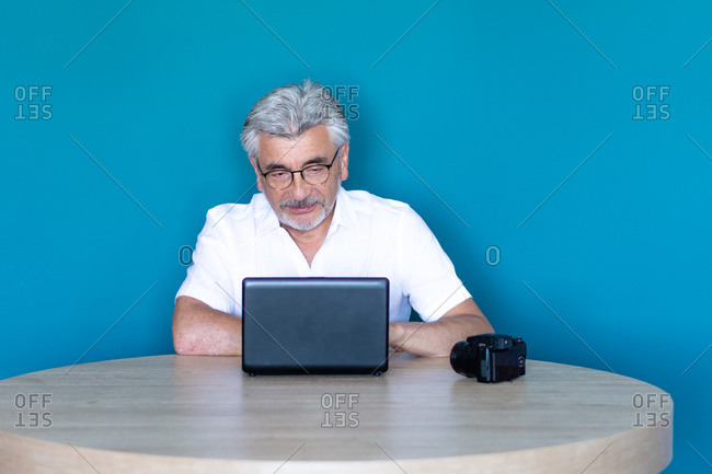 Older man with gray hair and glasses preparing for his trip from home with his laptop and camera.