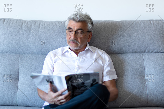 Older man with gray hair and glasses relaxing on his gray couch reading a magazine.