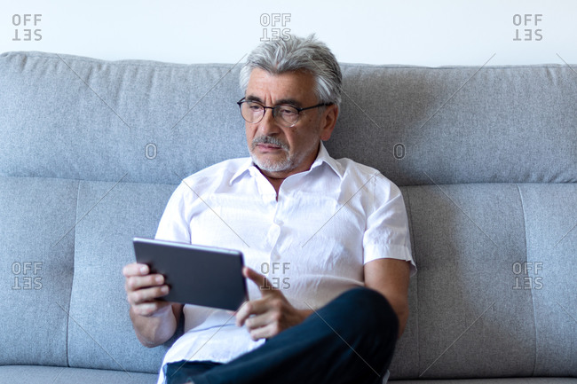 Older man with gray hair and glasses relaxing on his gray couch watching his tablet.