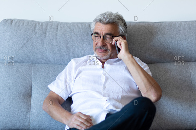 Older man with gray hair and glasses pensively taking a work call on his gray sofa.