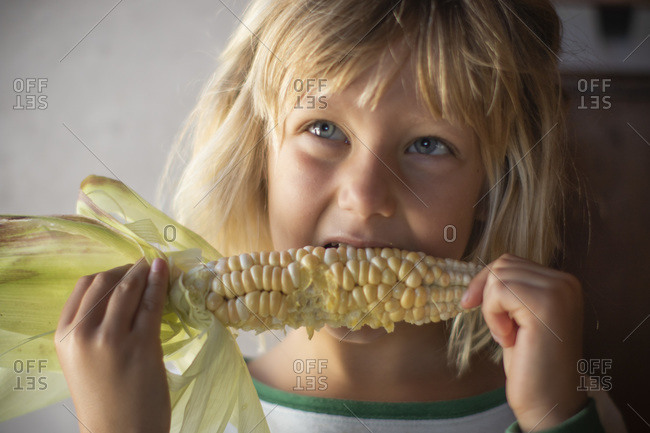 Young girl eating yellow corn while looking up