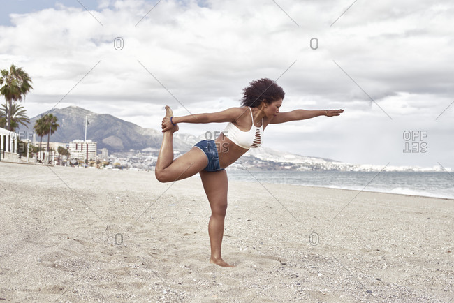 Black woman in short jeans poses on the beach balancing