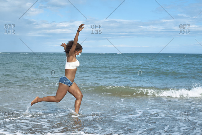 African-american woman with mask jumps on the sea