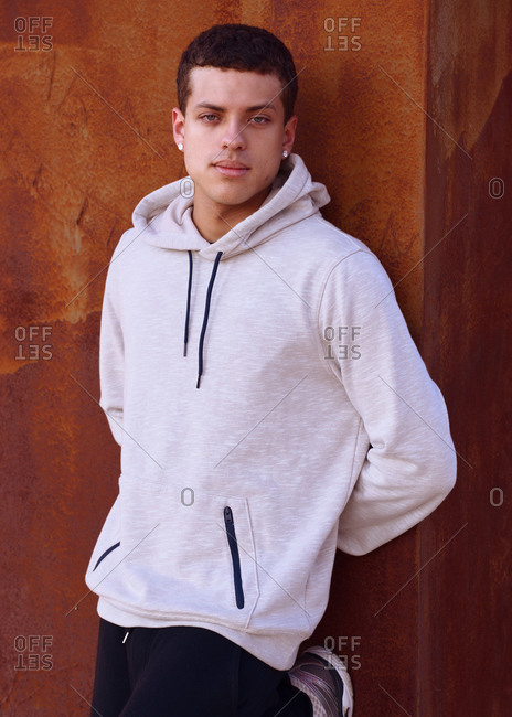 Handsome young latin american man leaning against a wall