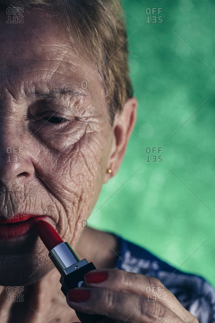 Mature woman in the foreground painting her lips in red