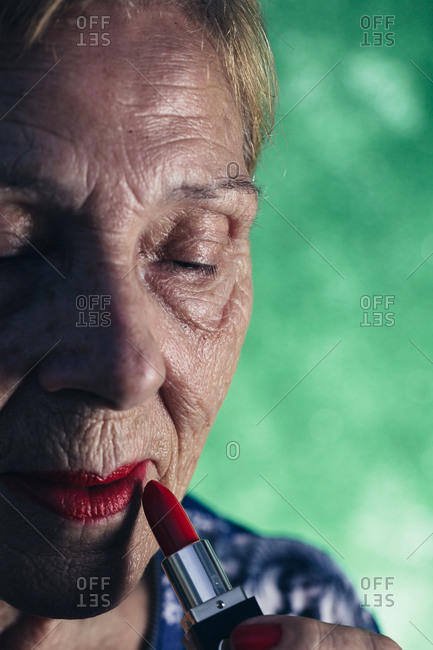 Old woman in the foreground wearing red lipstick on a green background