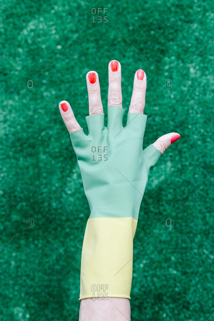 Elderly hand with broken rubber gloves showing red painted nails