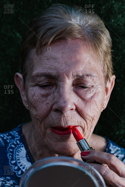Old woman painting her lips in red looking at herself in the mirror