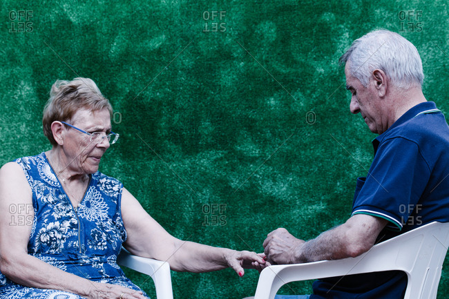 Old man painting his wife's nails red sitting on a plastic chair