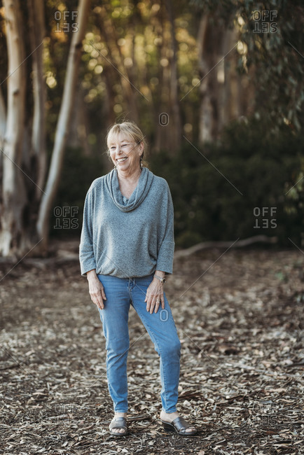 Portrait of senior adult woman smiling in forest