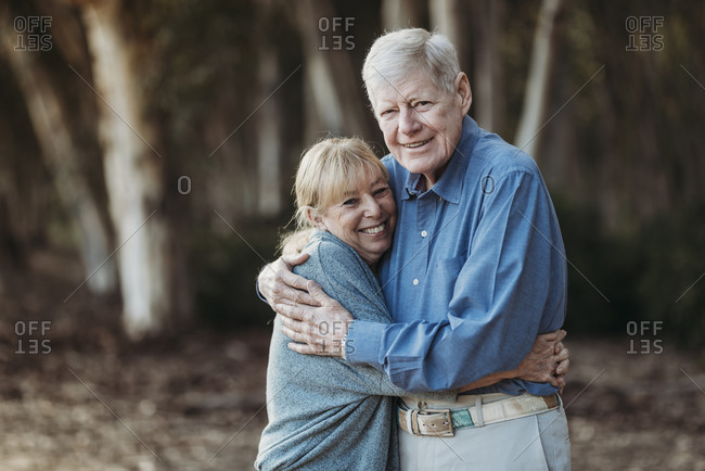 Portrait of retired adult couple hugging in forest