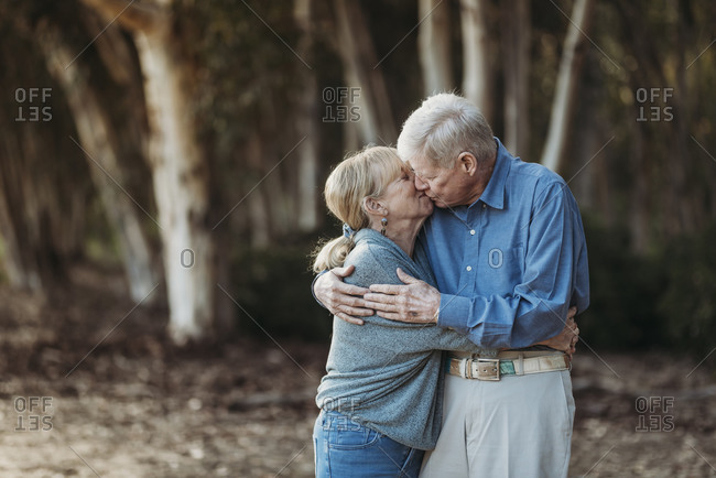 Portrait of senior adult retired couple kissing in forest