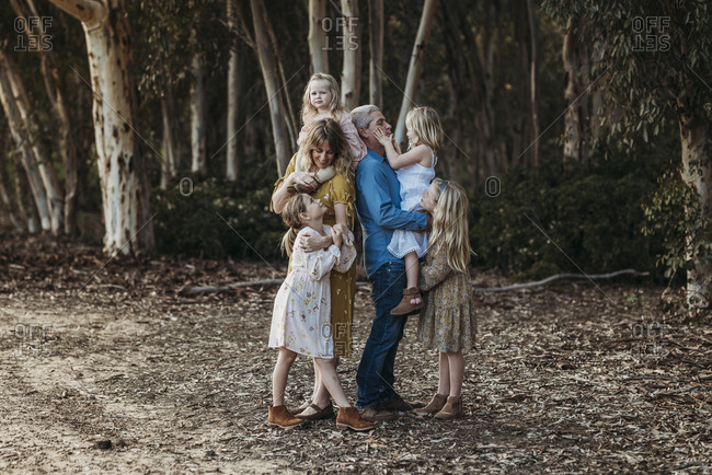 Lifestyle Portrait of Young Family Hugging Outside