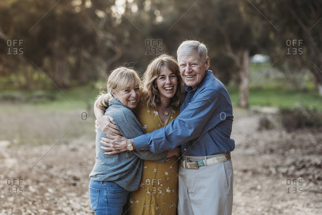 Portrait of adult woman and senior parents hugging at park