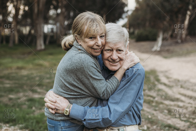 Close up portrait of senior adult couple hugging in forest