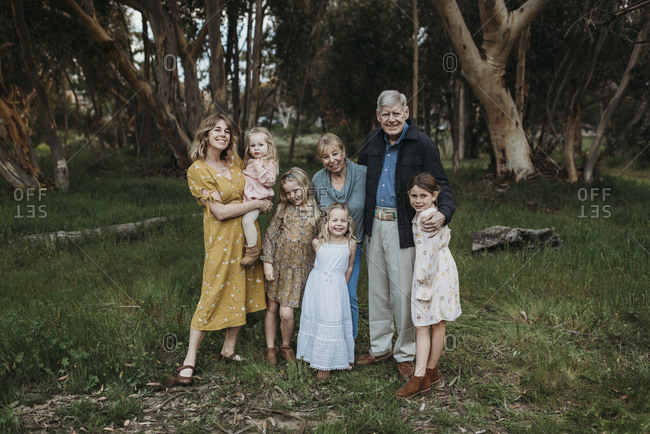Portrait of multigenerational family smiling and embracing in field