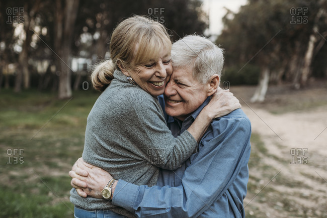 Close up portrait of senior adult couple embracing in forest