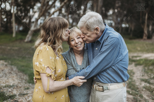 Senior mother being kissed by husband and adult daughter