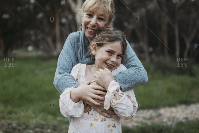 Close up of grandmother and granddaughter smiling in field