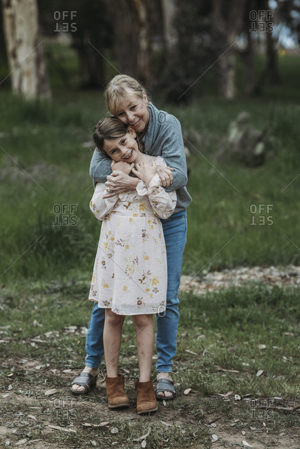 Grandmother and granddaughter embracing and smiling in field