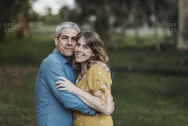 Portrait of married couple closely embracing and smiling in forest