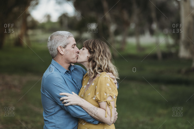 Portrait of married couple closely embracing and kissing outside