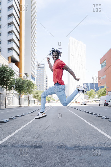 Excited ethnic man jumping on city street