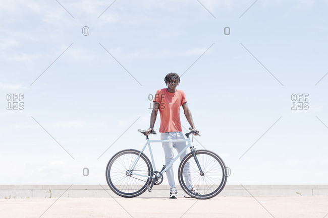 Happy young man with bicycle on street