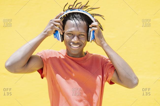 Cheerful black guy putting on headphones