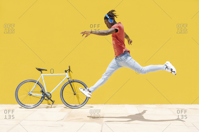Black male leaping near bicycle
