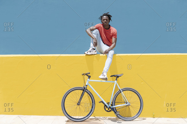 African American guy resting near bicycle