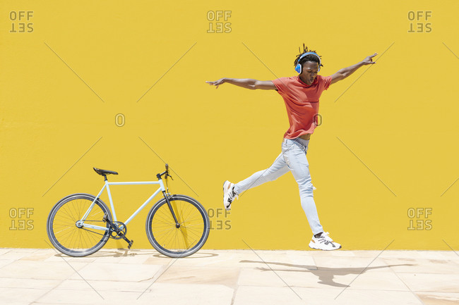 Energetic ethnic guy jumping near bicycle