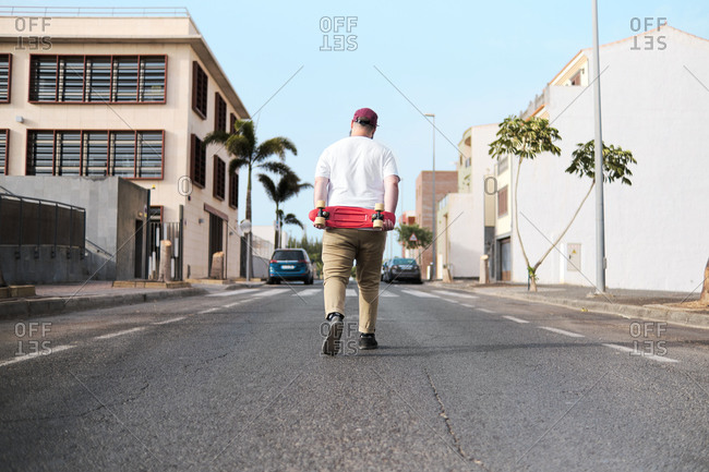Young man walking down the road holding his red skateboard on his back.