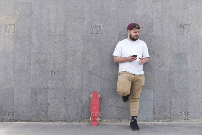 Young man with cell phone leaning against a wall next to pennyboard