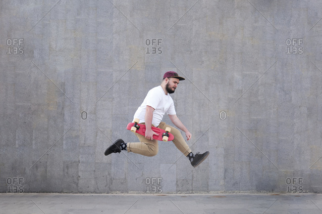 Young man jumping against a grey wall and holding his skateboard.