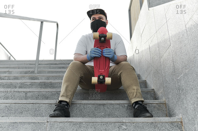 Young man with red skateboard sitting on the stairs