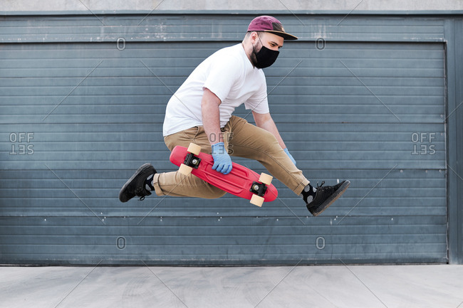 Young man jumping against a plain blue garage and holding hired skateboard.