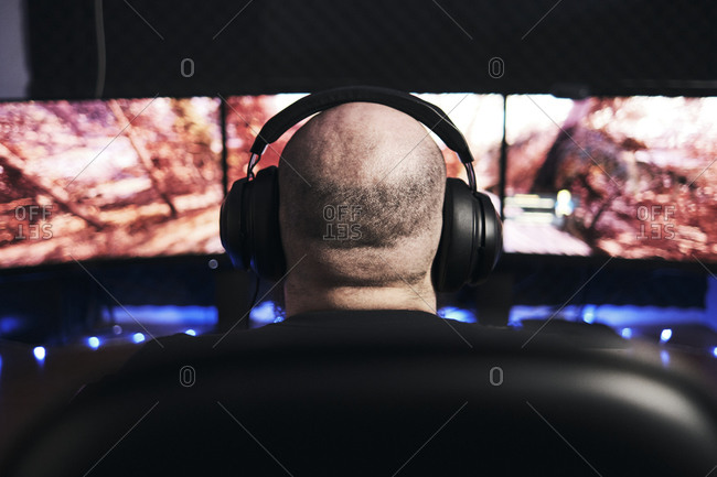 Man gamer playing video game wearing headphone.