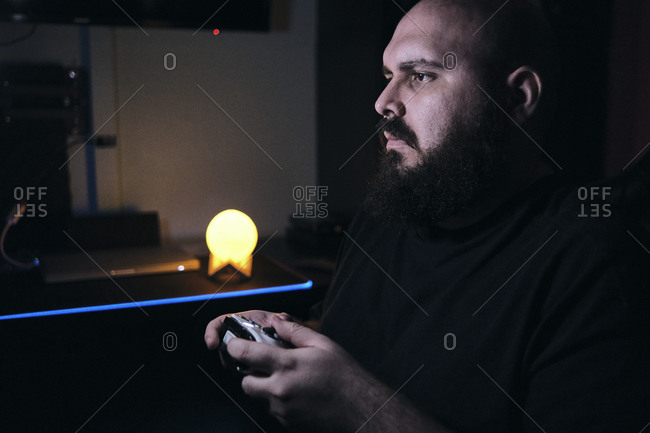 Adult gamer man playing in dark room