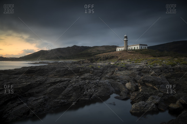 Lonely lighthouse on the coast at sunset