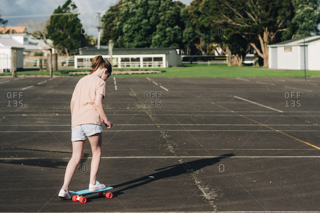 Young girl on a skateboard alone at a basketball court