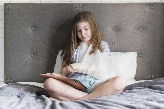 Girl sitting on bed with a broken arm in a sling looking at her device