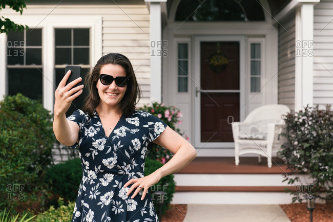 Adult woman smiling and taking selfie in front of home exterior