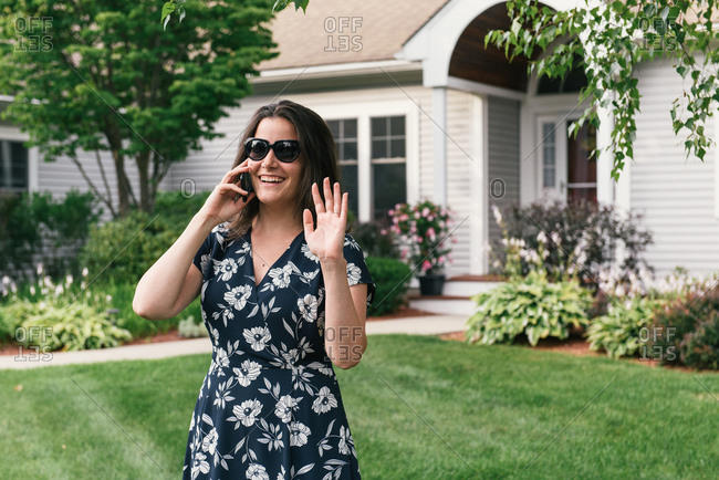 Woman on cell phone waving to neighbors in front of landscaped home