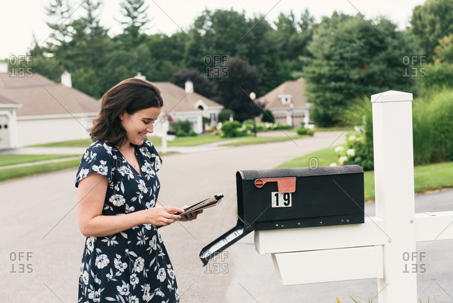 Woman checking mailbox and laughing at home in suburban neighborhood