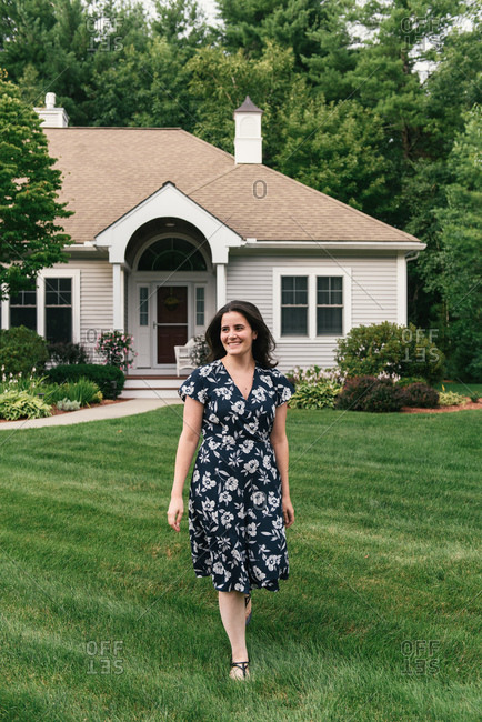 Smiling adult woman taking a stroll in front of suburban home