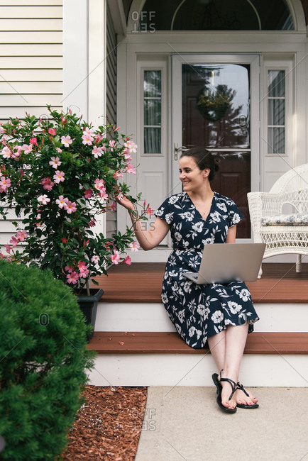 Woman working from home exterior on laptop and smiling with flowers