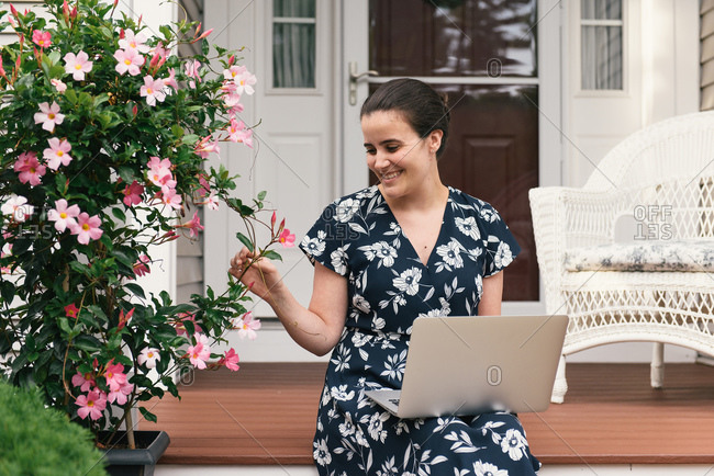 Half crop of woman sitting with laptop from remote work from home