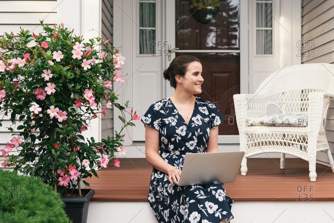 Adult woman sitting on front steps of home exterior with laptop