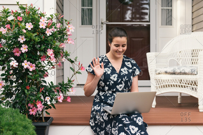 Adult woman laughing and waving to co-worker on remote meeting at home